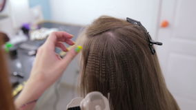 Hairdresser using straightener on long hair of client in hair salon stock video footage