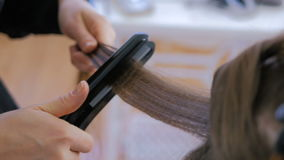 Hairdresser using straightener on long hair of client in hair salon stock video
