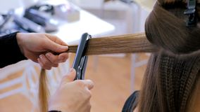 Hairdresser using straightener on long hair of client in hair salon. Professional hairdresser, stylist doing hairstyle and using straightener on beautiful long Stock Images