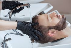 The hairdresser washes the head of the young man with shampoo after haircuts. In the hairdresser Royalty Free Stock Photo
