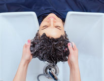 The hairdresser washes the shampoo off the hair to a young girl Royalty Free Stock Images