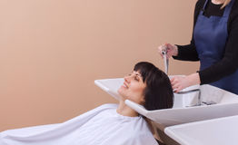 The hairdresser washes the shampoo off the hair to a young girl, brunette Royalty Free Stock Images