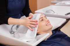 The hairdresser washes the shampoo off the hair to a young girl. Brunette in a beauty salon Royalty Free Stock Images