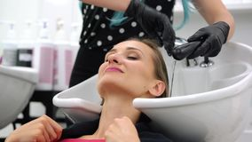 Hairdresser washing hair of client in her shop. In wash basin stock video