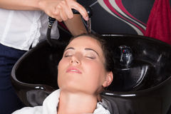 Hairdresser washing hair of customer in salon Royalty Free Stock Photos