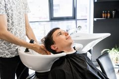 Hairdresser washing hair to his handsome client. Barber at work. Man at barbershop. royalty free stock images