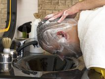 Hairdresser washing hair to man after haircut in barber shop stock photo