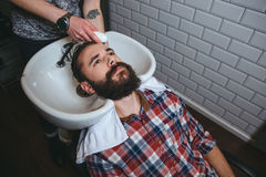 Hairdresser washing hair of young man with beard. Hairdresser washing hair of young attractive man with beard in checkered shirt in hairdressing salon Stock Photo