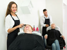 Hairdresser washing head of adult woman Royalty Free Stock Photo