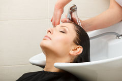Hairdresser washing her woman customer hair Royalty Free Stock Photography