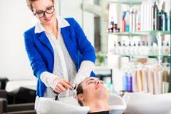 Hairdresser washing man hair in barbershop. Female coiffeur washing men hair in hairdresser shop royalty free stock photography