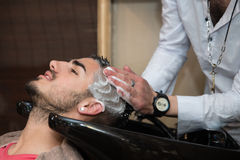 Hairdresser Washing Man Head In Barber Shop Stock Photography