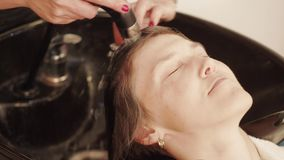 Hairdresser washing woman hair before haircut in back bar. Of barbershop. Barber hands wash head for head-dress in shampoo unit. Preparing for style haircut stock footage