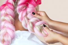 The hairdresser weaves braids with pink kanekalons beautiful blonde. Beauty salon stock images