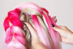 The hairdresser weaves braids with pink kanekalons beautiful blonde. In a beauty salon stock photo