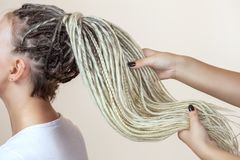 A hairdresser weaves dreadlocks to a beautiful young girl. In a hairdresser`s stock photography
