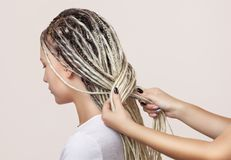 A hairdresser weaves dreadlocks to a beautiful young girl in a hairdresser`s.  royalty free stock photos