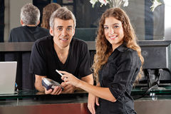 Hairdresser With Woman Paying Through Cellphone At Royalty Free Stock Images