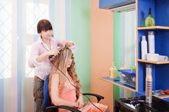 Hairdresser-womens makes hair young woman Royalty Free Stock Photos