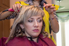 Hairdresser-womens makes hair young woman Stock Images
