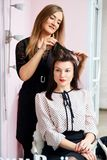 Hairdresser at work - the hairdresser does the hair of a beautiful young brunette to the client in beauty salon. Hairdresser at work - the hairdresser does the royalty free stock photo