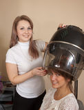 Hairdresser working with hair dryer Royalty Free Stock Photography