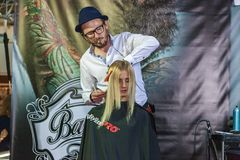Hairdresser works with a model at the exhibition Stock Photography