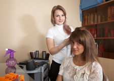 Hairdresser works on woman hair Royalty Free Stock Images