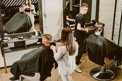 Hairdressers cut their clients in the salon. Hairdressers hairstyle their clients in the salon royalty free stock photography