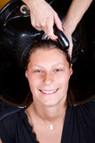 Hairdressers hand washing female customer's hair in salon Stock Photography