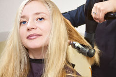 Hairdressers hands drying long blond hair Royalty Free Stock Images