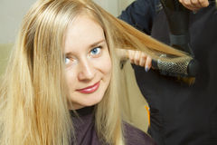Hairdressers hands drying long blond hair Royalty Free Stock Photo