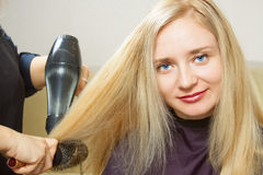 Hairdressers hands drying long blond hair Stock Photos