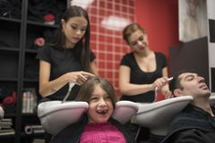 Hairdressers with little girls and man. Father and daughter at h royalty free stock photos