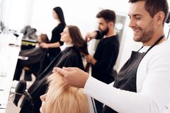 Hairdressers make haircut for women of different age categories in beauty salon. royalty free stock photography