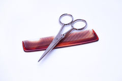 Hairdressers' scissors and comb on a white background. Stock Photography