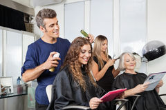 Hairdressers Setting Up Client's Hair In Salon. Male and female hairdressers setting up client's hair in beauty salon royalty free stock images