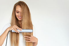 hairdressing Γυναίκα με όμορφο μακρυμάλλες χρησιμοποιώντας Straightener στοκ φωτογραφία