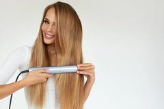 hairdressing Donna con bei capelli lunghi facendo uso del raddrizzatore Fotografie Stock Libere da Diritti