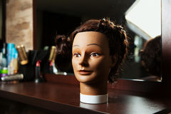 Hairdressing mannequin located on a wooden table. Female hairdressing mannequin is located on a wooden table, hairdressing tools on the background royalty free stock photos