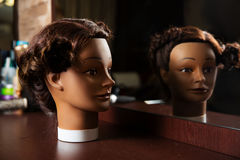 Hairdressing mannequin located on a wooden table. Female hairdressing mannequin is located on a wooden table, hairdressing tools on the background royalty free stock photo