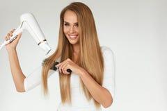 hairdressing Mulher que seca o cabelo reto longo saudável bonito Fotos de Stock