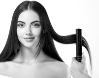 Hairdressing Process. Girl Model Hair Straightening Irons.Beautiful Woman With Long Straight Hair. Healthy Hair. Royalty Free Stock Photography