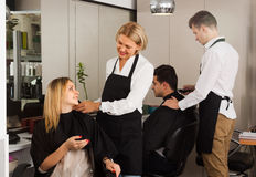 Hairdressing saloon. Woman and men hairdressers cuts women and men at the hairdresser saloon royalty free stock photo