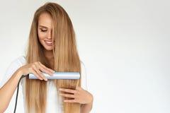 hairdressing Vrouw met Mooi Lang Haar die Gelijkrichter met behulp van stock fotografie