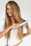 Hairdressing. Woman With Beautiful Long Hair Using Straightener. Hairdressing. Woman With Beautiful Long Straight Hair Using Hair Straightener. Gorgeous Smiling Stock Images