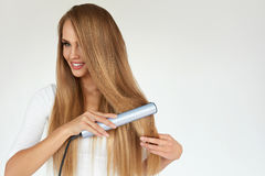 Hairdressing. Woman With Beautiful Long Hair Using Straightener Stock Images