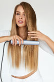 Hairdressing. Woman With Beautiful Long Hair Using Straightener. Hairdressing. Woman With Beautiful Long Straight Hair Using Hair Straightener. Gorgeous Smiling Stock Photo