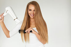 Hairdressing. Woman Drying Beautiful Healthy Long Straight Hair Royalty Free Stock Photography