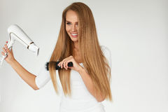 Hairdressing. Woman Drying Beautiful Healthy Long Straight Hair Stock Images